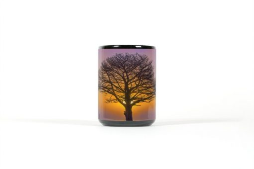 Center view of black mug with a tree silhouetted by a sunset